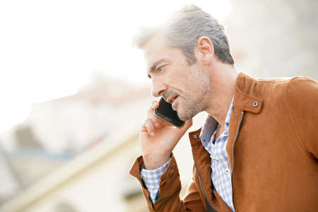 Smiling mature businessman talking on phone in the street Stock Photo