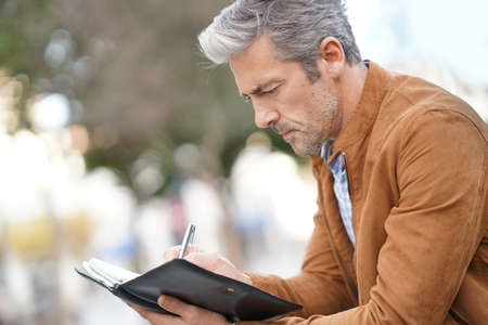 Businessman sitting on public bench, working with digital tablet