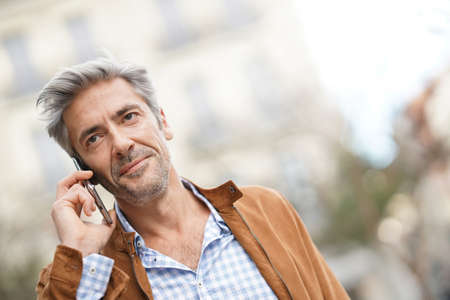 Mature handsome man in the street, talking on phone