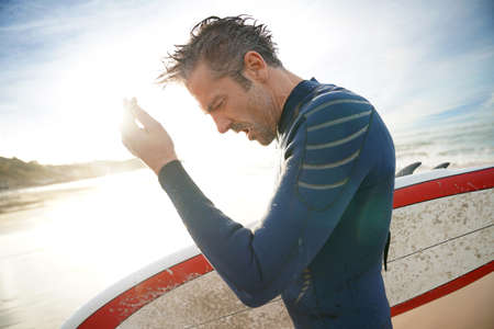 getting out: Surfer getting out of the water after session Stock Photo