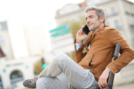 Man talking on phone sitting on public bench Stock Photo