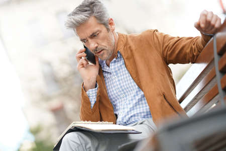 telephone salesman: Businessman sitting on public bench, scheduling working day Stock Photo