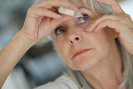 woman eye: Senior woman putting eye drop