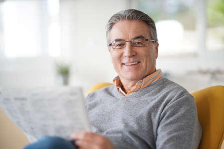 Smiling senior man with eyeglasses reading newspaper Stock Photo