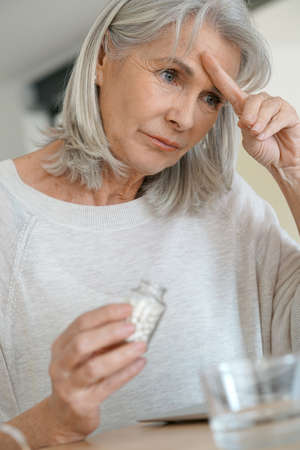 taking medicine: Senior woman taking pill to ease migraine