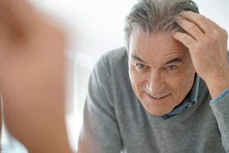 senior men: Senior man looking at hair in mirror