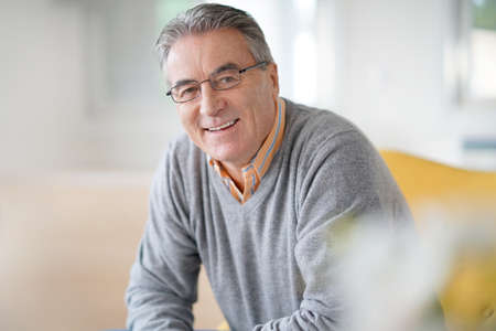 Smiling senior man with eyeglasses relaxing in armchair Stock Photo