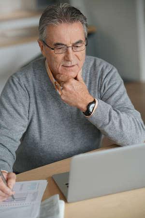 senior men: Senior man at home connected on laptop computer Stock Photo