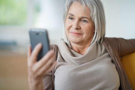 senior woman: Senior woman relaxing and using smartphone