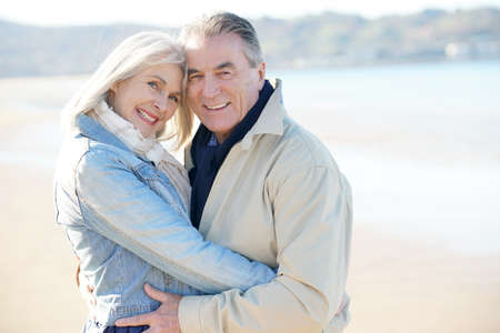 wintertime: Portrait of senior couple having fun at the beach, wintertime