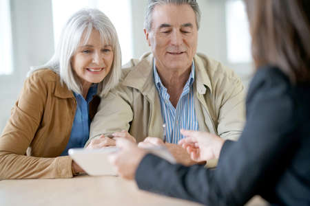 Senior couple meeting financial adviser for investment Stock Photo