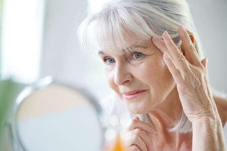 Retrato de la mujer mayor que aplica la crema anti-envejecimiento Foto de archivo - 69034035