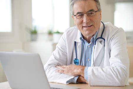 medicalcare: Portrait of senior doctor sitting in medical office