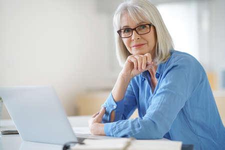 Ältere Geschäftsfrau, die im Büro arbeiten
