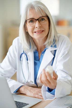 medicalcare: Senior female doctor giving prescription to patient