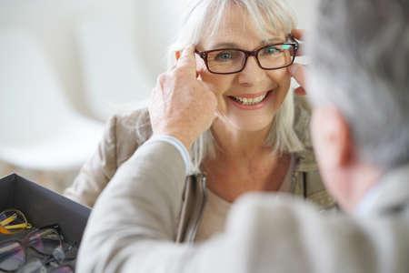 Mujer mayor en las tiendas tratando óptico de las lentes de Foto de archivo - 68984018