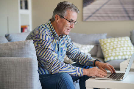 using computer: Senior man in living-room using laptop computer