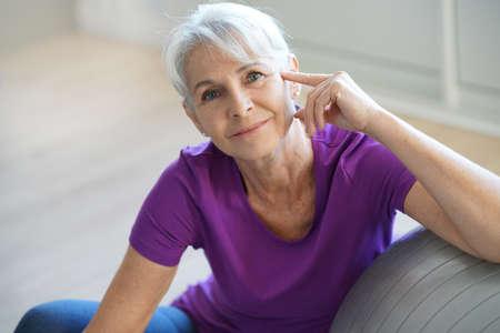 senior women: Senior woman sitting by fitness ball