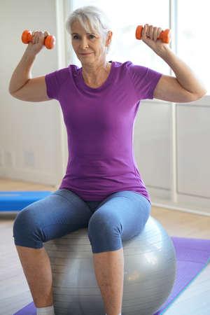 persona mayor: Mujer mayor que hace ejercicios de acondicionamiento físico delante de la TV Foto de archivo