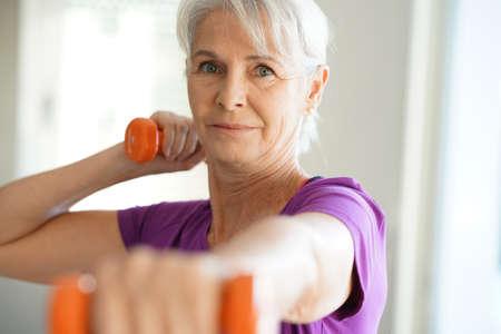 ダンベルを持ち上げる年配の女性の肖像画 写真素材