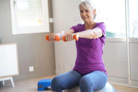 Ältere Frau Fitness-Übungen vor dem Fernseher zu tun