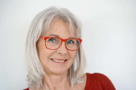 Portret van senior vrouw met rode overhemd en bril, geïsoleerde Stockfoto