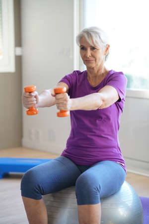 exercices: Senior woman doing fitness exercices in front of tv Stock Photo