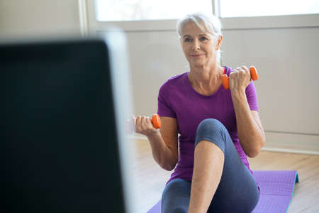 senior exercising: Senior woman doing fitness exercices in front of tv Stock Photo