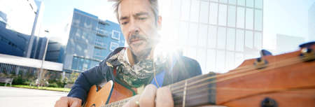 playing folk: Mature trendy guy playing the guitar in the street Stock Photo