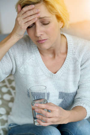 Middle-aged woman at home taking pill to ease headache Stock Photo