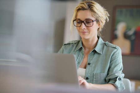 パソコンで自宅で仕事金髪女性の肖像