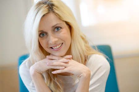 Portrait of middle-aged blond woman relaxing at home