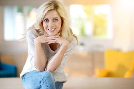 mujer sentada: Mujer rubia con los ojos azules sentado en la mesa Foto de archivo