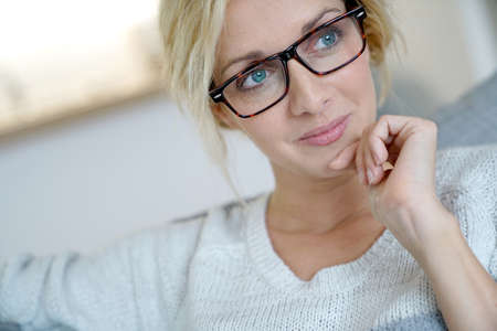 portrait of beautiful blond woman relaxing in sofa at home Stock Photo
