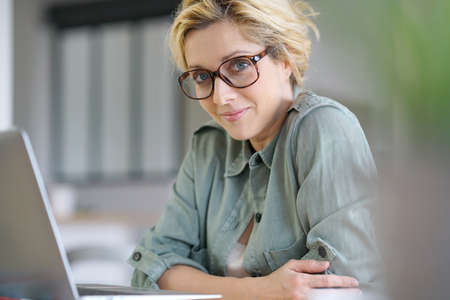 homeoffice: Portrait of blond woman working from home on laptop computer