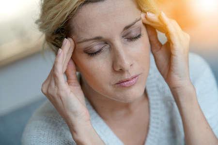 片頭痛を持つ金髪の中年の女性の肖像画