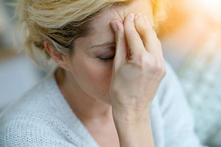 medicalcare: Portrait of middle-aged blond woman having a migraine Stock Photo