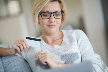 Middle-aged woman at home buying on internet with credit card