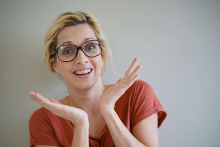 Blond woman with eyeglasses having a surprised look Stock Photo