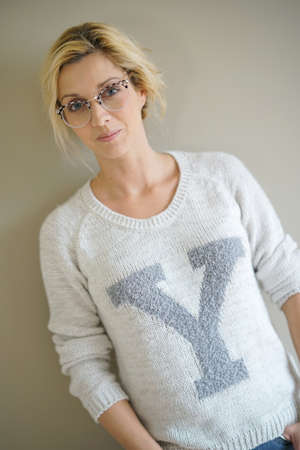 Portrait of beautiful blond woman with eyeglasses standing on grey background Stock Photo - 71634391