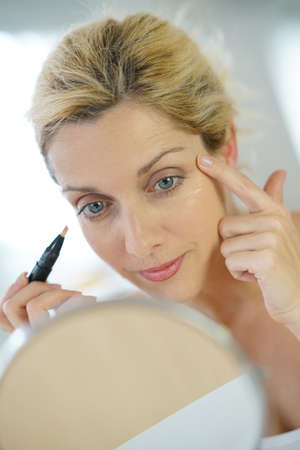 40 years: Middle-aged blond woman putting eye concealer in front of mirror Stock Photo