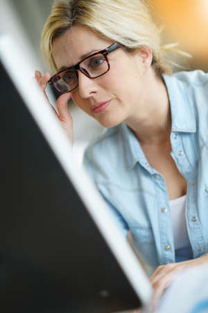 officeworker: Businesswoman in office working on desktop computer Stock Photo