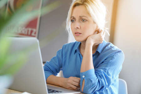 homeoffice: Portrait of blond woman with blue shirt working from home on laptop