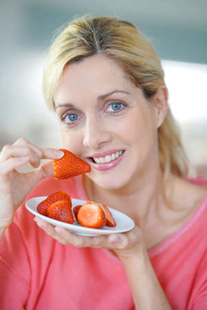 Portrait of blond middle-aged woman eating strawberries