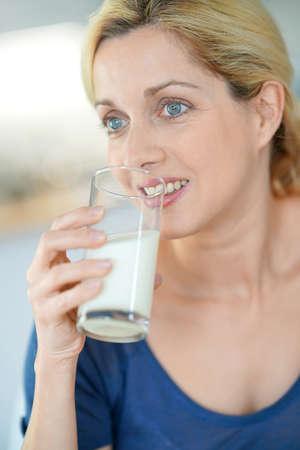 tomando leche: Portrait of blond mature woman drinking milk from glass