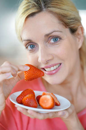 woman diet: Portrait of blond middle-aged woman eating strawberries