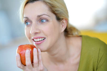 diet food: Portrait of blond woman eating an apple Stock Photo