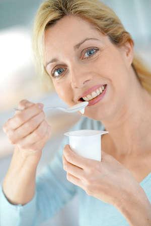 eating yogurt: Portrait of blond woman eating yogurt Stock Photo