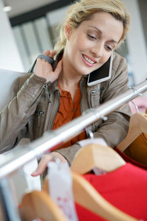 Woman talking on phone with friend while shopping in clothing store