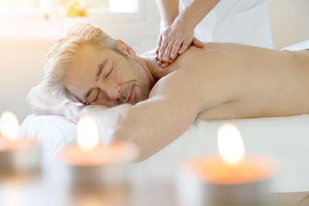 Hombre que se relaja en mesa de masaje que recibe el masaje Foto de archivo